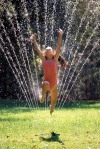Girl jumps through water sprinkler.